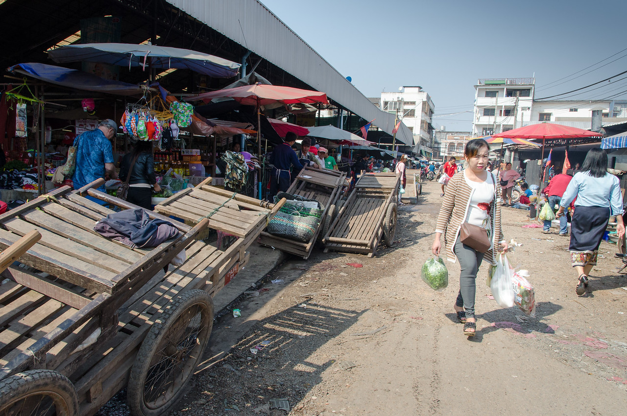 A woman walks past carts with her purchases.