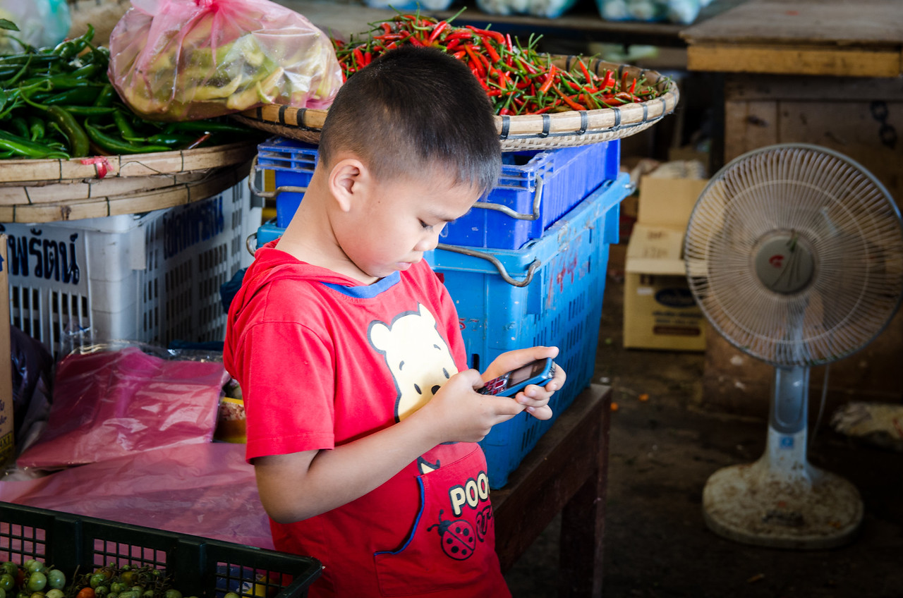 This boy is playing with a phone while his mother works.