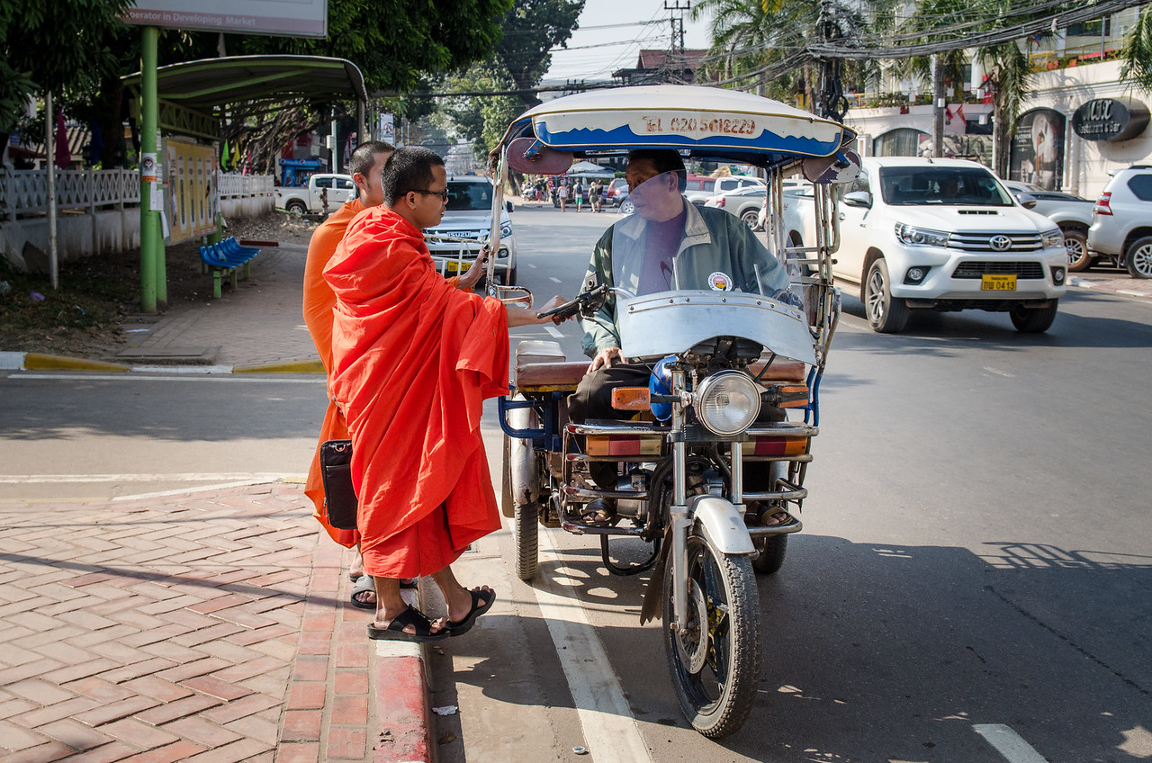 Monks chatting with a tuk-tuk driver.