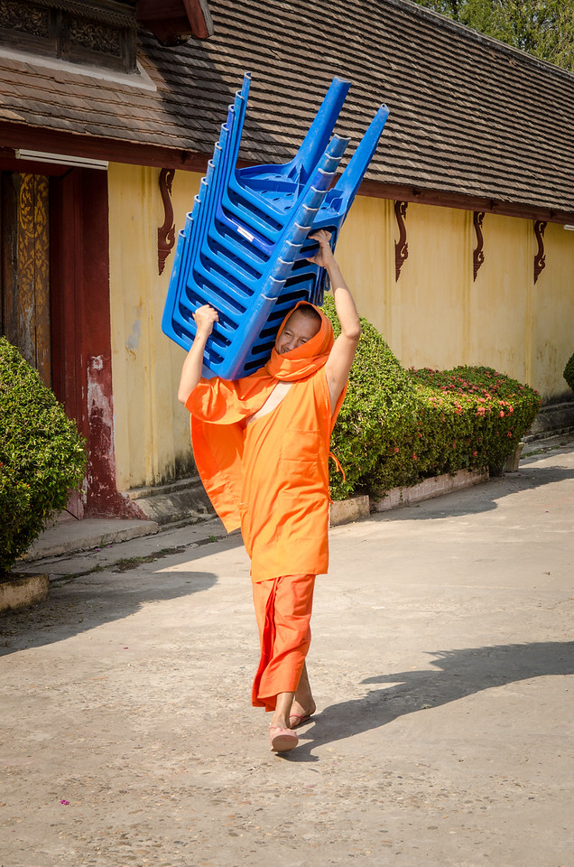 Monk carrying plastic chairs.