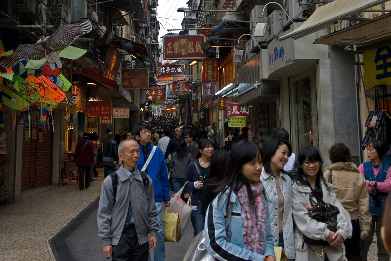 Locals and tourists in a busy side street at the City Center - Macau