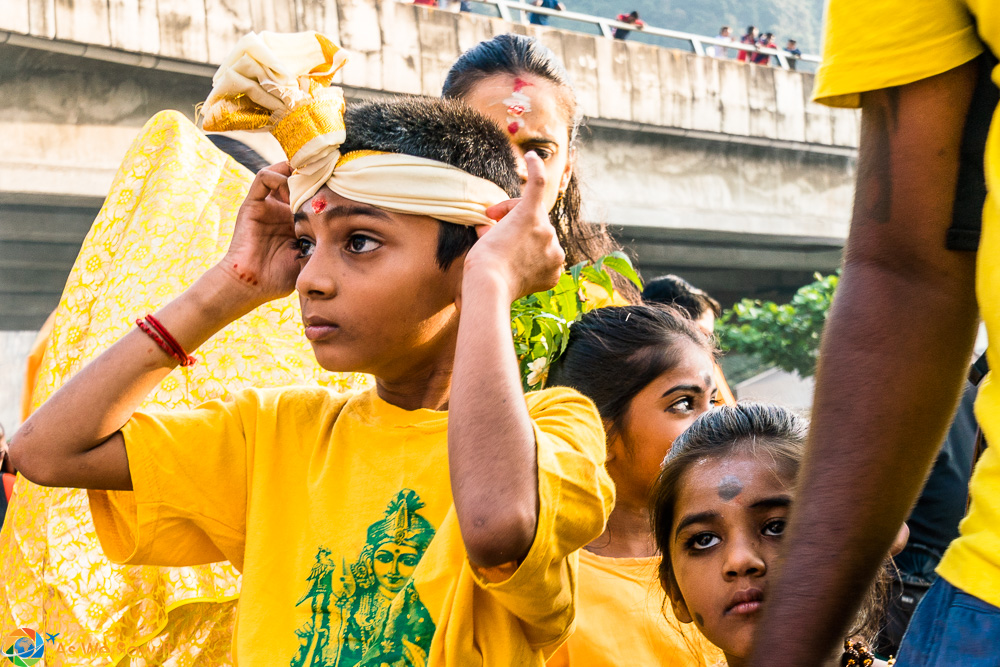 Young boy adjusts his head dress for Thaipusam 2017