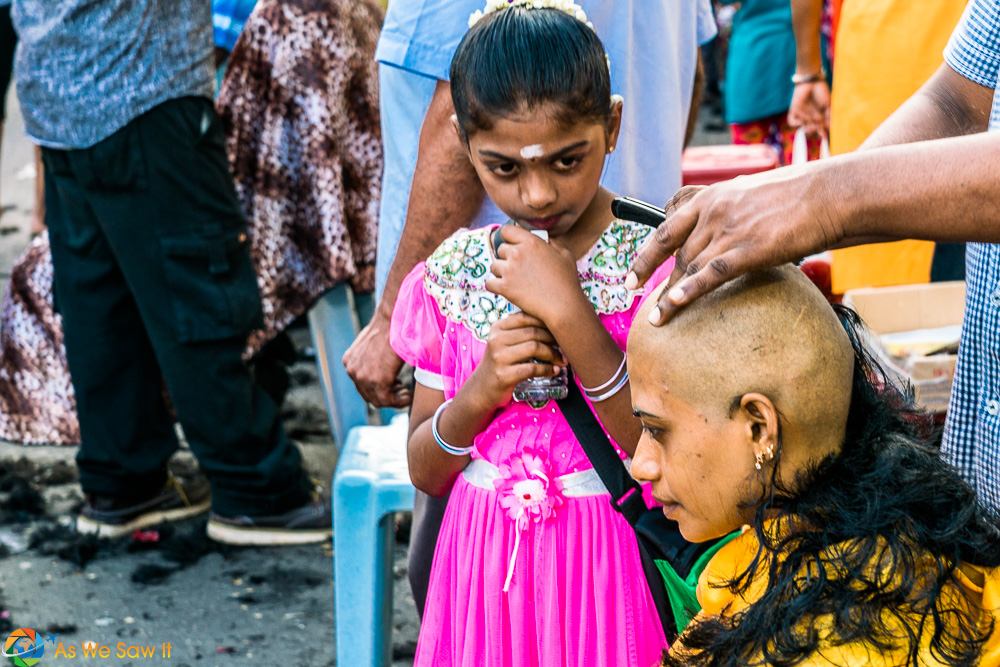 Mother having her head shaved as her daughter looks on, both in tears. Thaipusam 2017