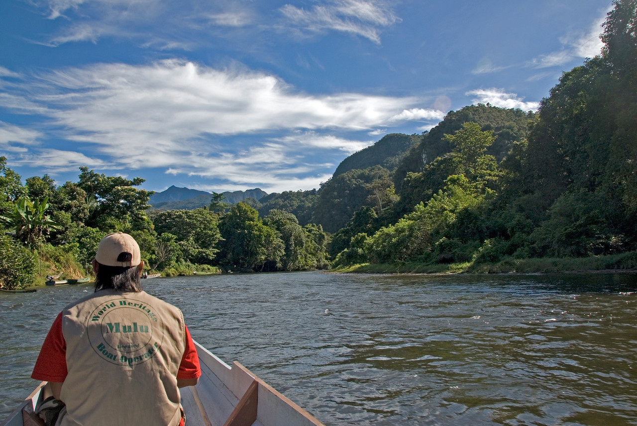 Riding on a boat with view of the nearby rainforest and mountain at Mulu National Park - Sarawak, Malaysia