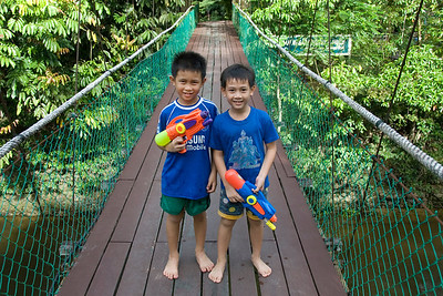 Two boys holding water guns on on Mulu Bridge, Mulu National Park - Sarawak, Malaysia