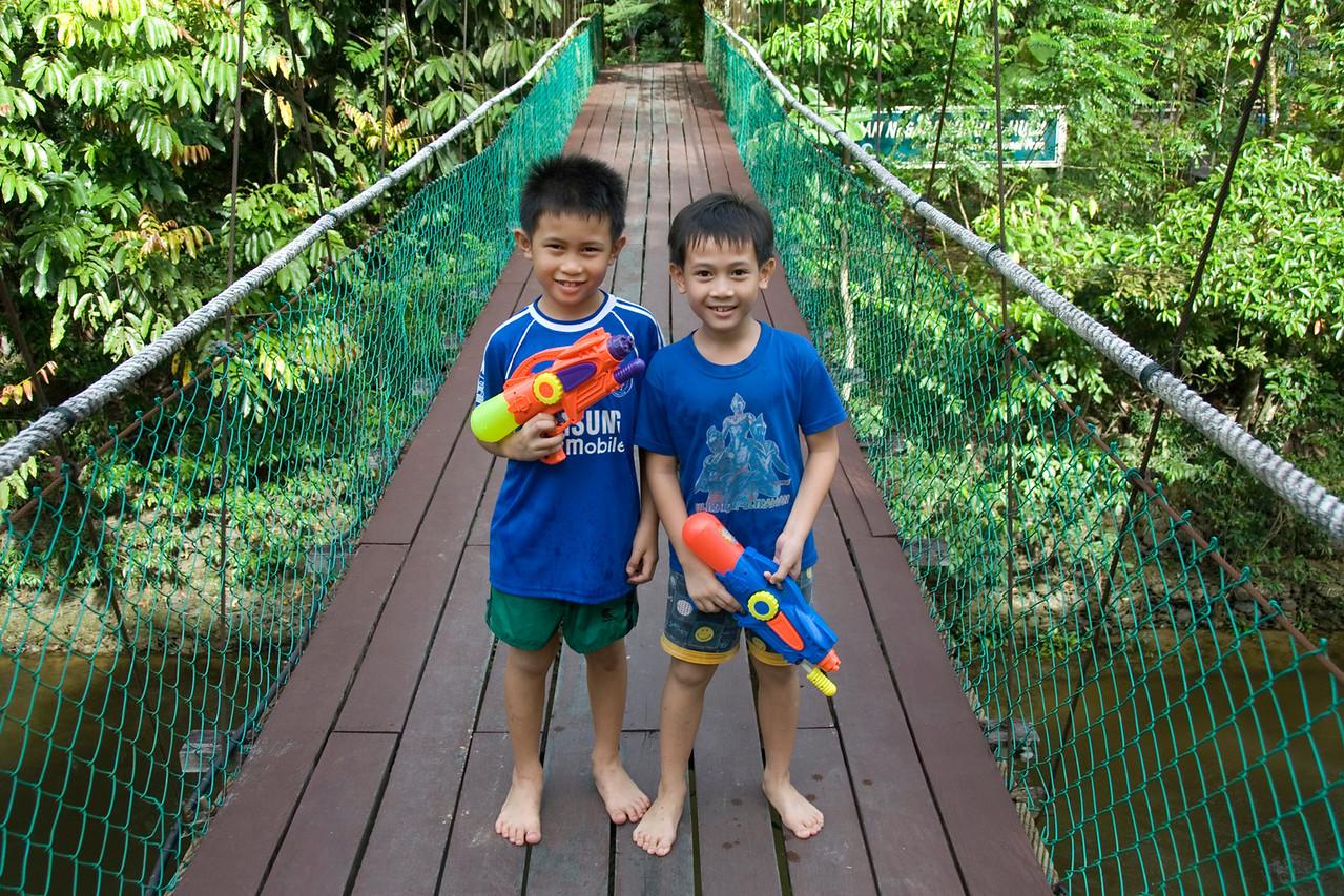 Two boys holding water guns on on Mulu Bridge, Mulu National Park - Sarawak, Malaysia