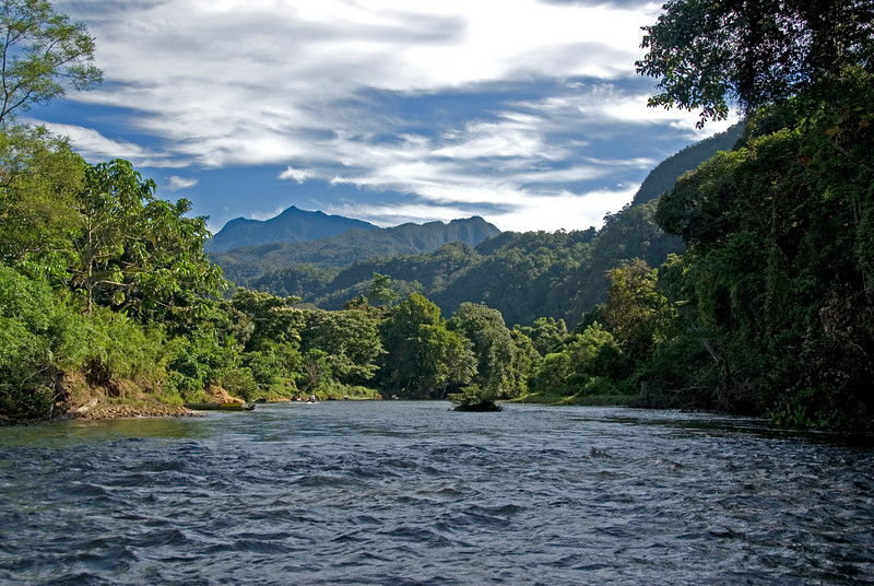 Calm river against lush greens and mountains in Mulu National Park - Sarawak, Malaysia