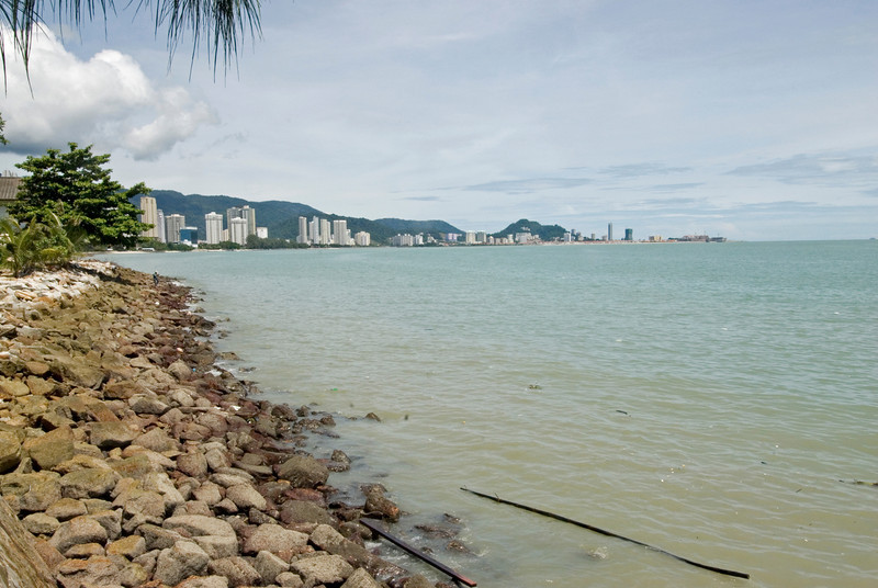 Calm sea water and shore with a view of skyline at George Town, Penang, Malaysia