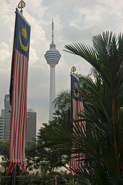 The Kuala Lumpur Tower towering above buildings and flags in Kuala Lumpur, Malaysia