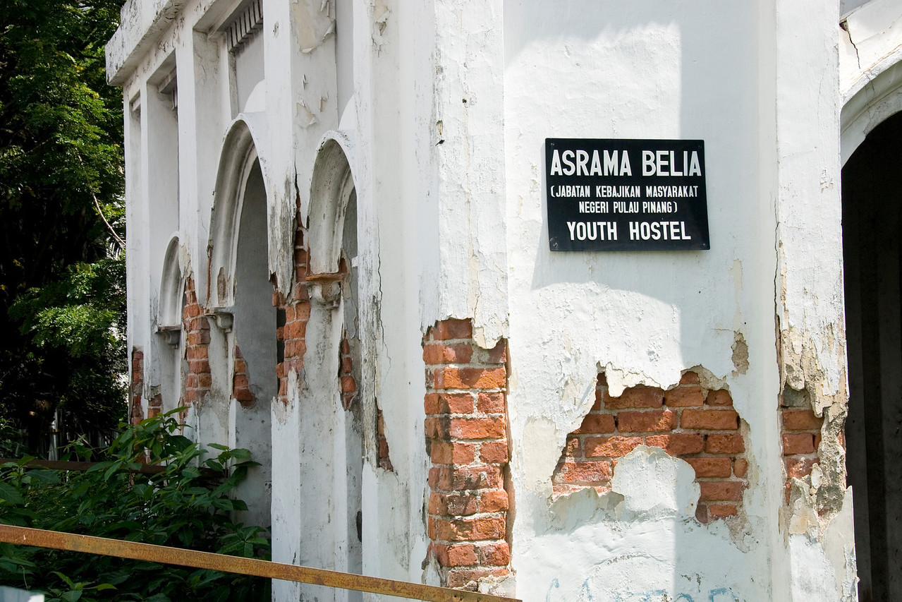 Sign on the wall of the ruined youth hostel building - George Town, Penang, Malaysia