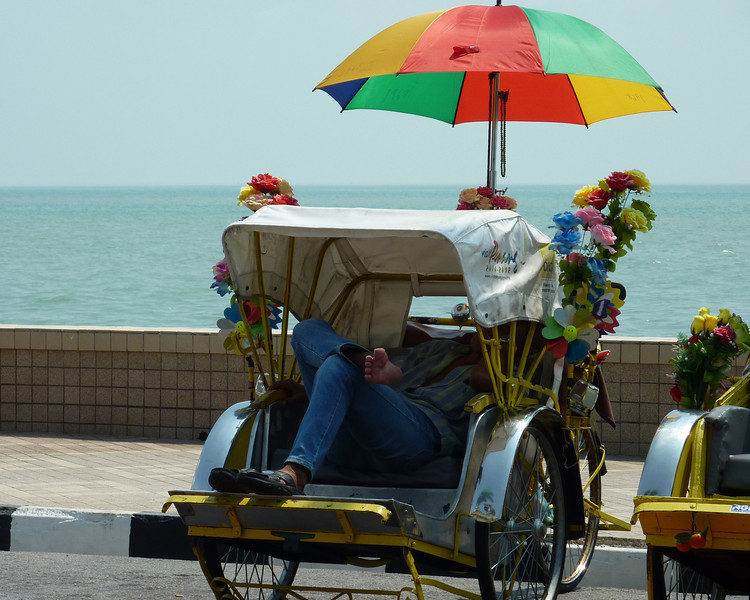 A rickshaw driver taking a mid-day break by the beach in Penang, Malaysia.