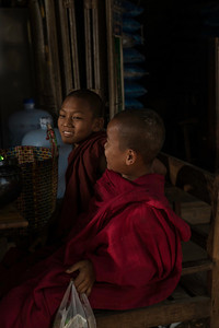 Two young monks rest in the market with a small bag of donated goodies.
