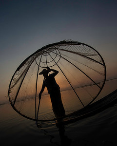 Now he's standing to demonstrate the traditional Inle Lake fishing net.