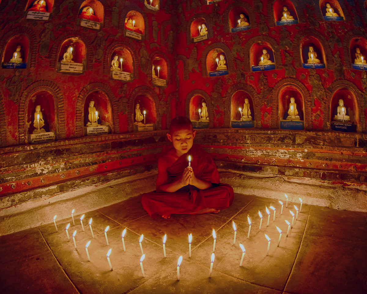 A dramatic sight as a young monk prays surrounded by candle light