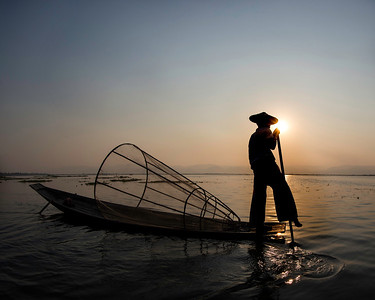 Fishing with a traditional net and rowing with his leg, this gentleman cast a distinct shadow as her worked his boat on Inle Lake