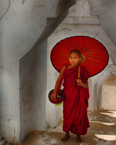 This young monk was not really happy posing with the umbrella in the stairway.