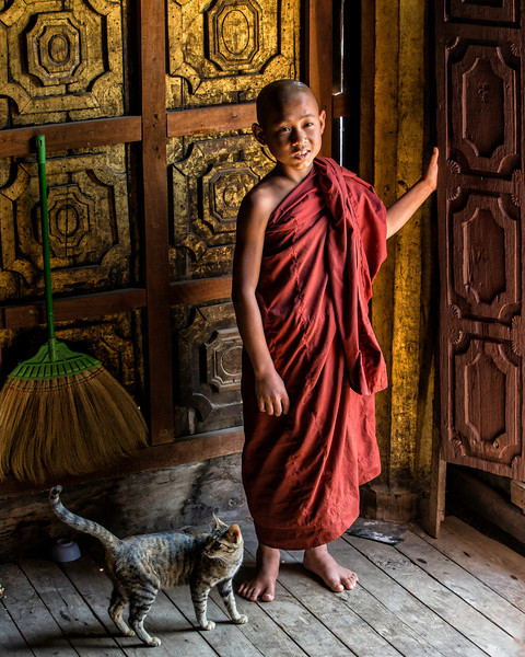 "This young monk posed at the door on his way to ""let the cat out."""