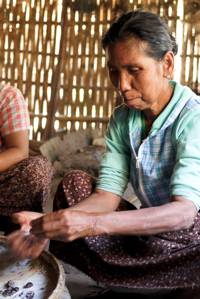 A woman rolls sour plum candies in sugar for sale in Bagan, Burma (Myanmar)