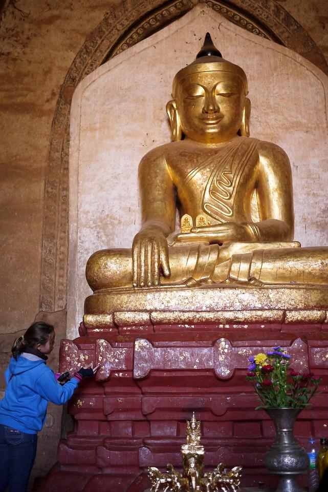 Ana applies gold leaf to a Buddha in Bagan, Burma (Myanmar)