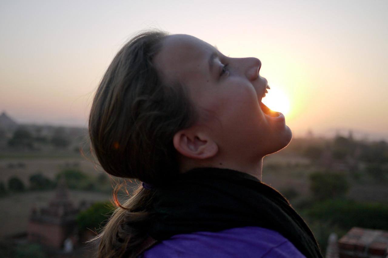 Ana tries to eat the sun at sunset in Bagan, Burma (Myanmar)
