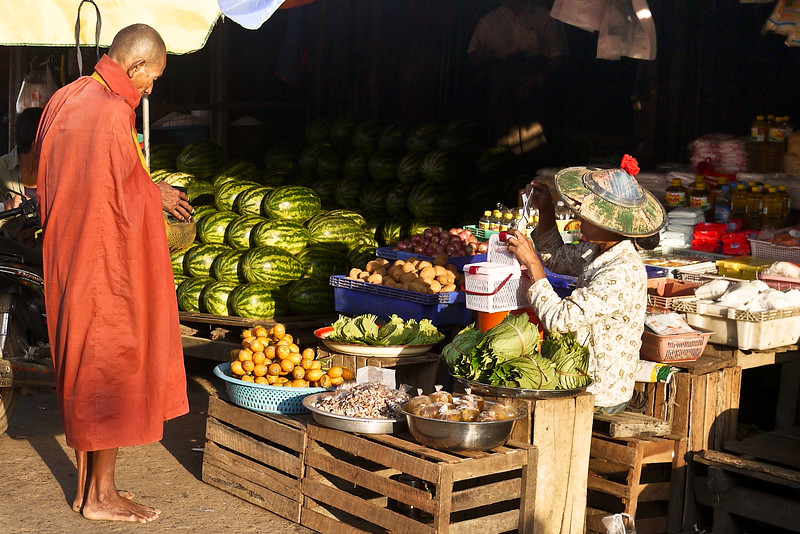 A monk takes alms in the early morning sunshine at the market in Hpa-An, Burma.