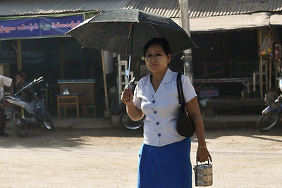 A women takes her lunch pail on her way to work, taking cover from the sun with an umbrella in Hpa-An, Burma.