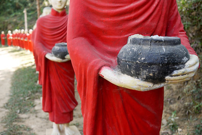Statues of monks and their alms bowls near in Hpa-An, Burma outside of the Kaw Ka Taung Cave.