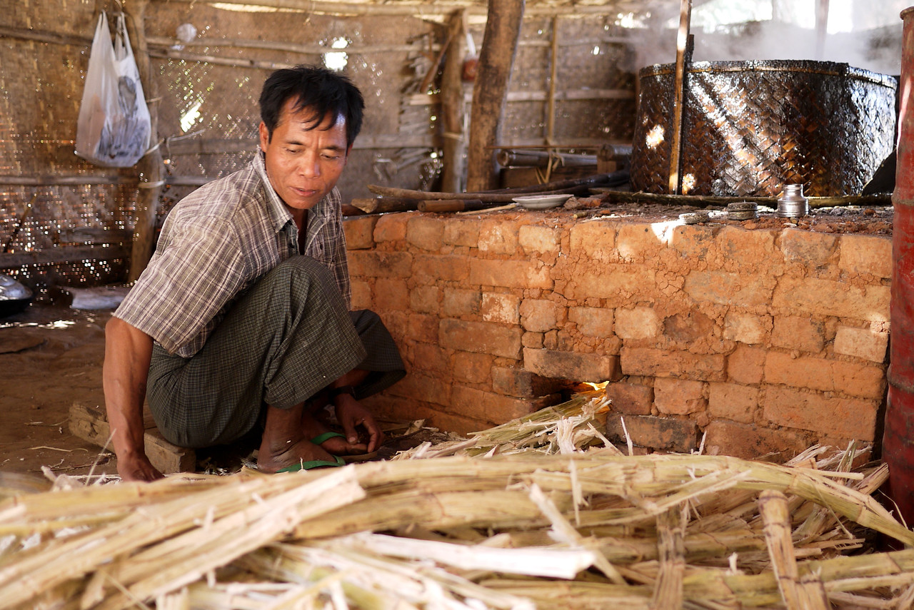 Stoking the fire to boil the sugarcane juice Inle Lake, Burma (Myanmar).