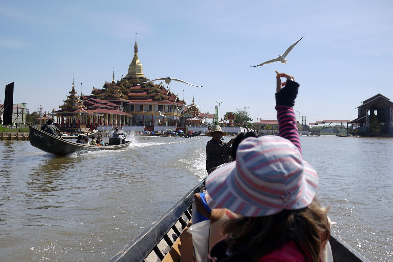 Ana holds out her hand to feed the seagulls on Inle Lake, Burma (Myanmar).