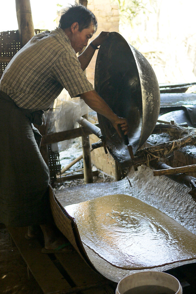 The family spreads the very think sugarcane juice so it can dry into jaggery candies, Inle Lake, Burma (Myanmar).