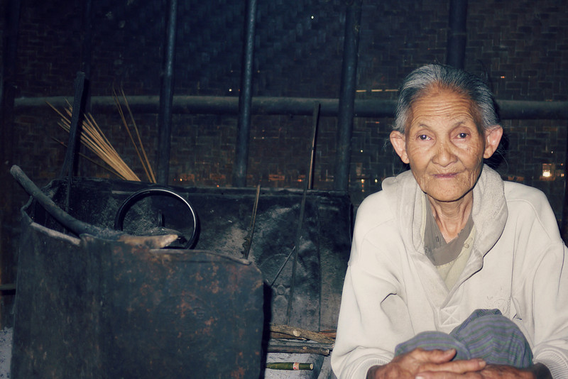An elderly grandmother looks on at our group, and keeps the tea hot and boiling while we visit her house, on Inle Lake, Burma (Myanmar).