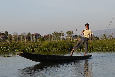 A fisherman does the signature one-legged paddle on the canals of Inle Lake, Burma (Myanmar).