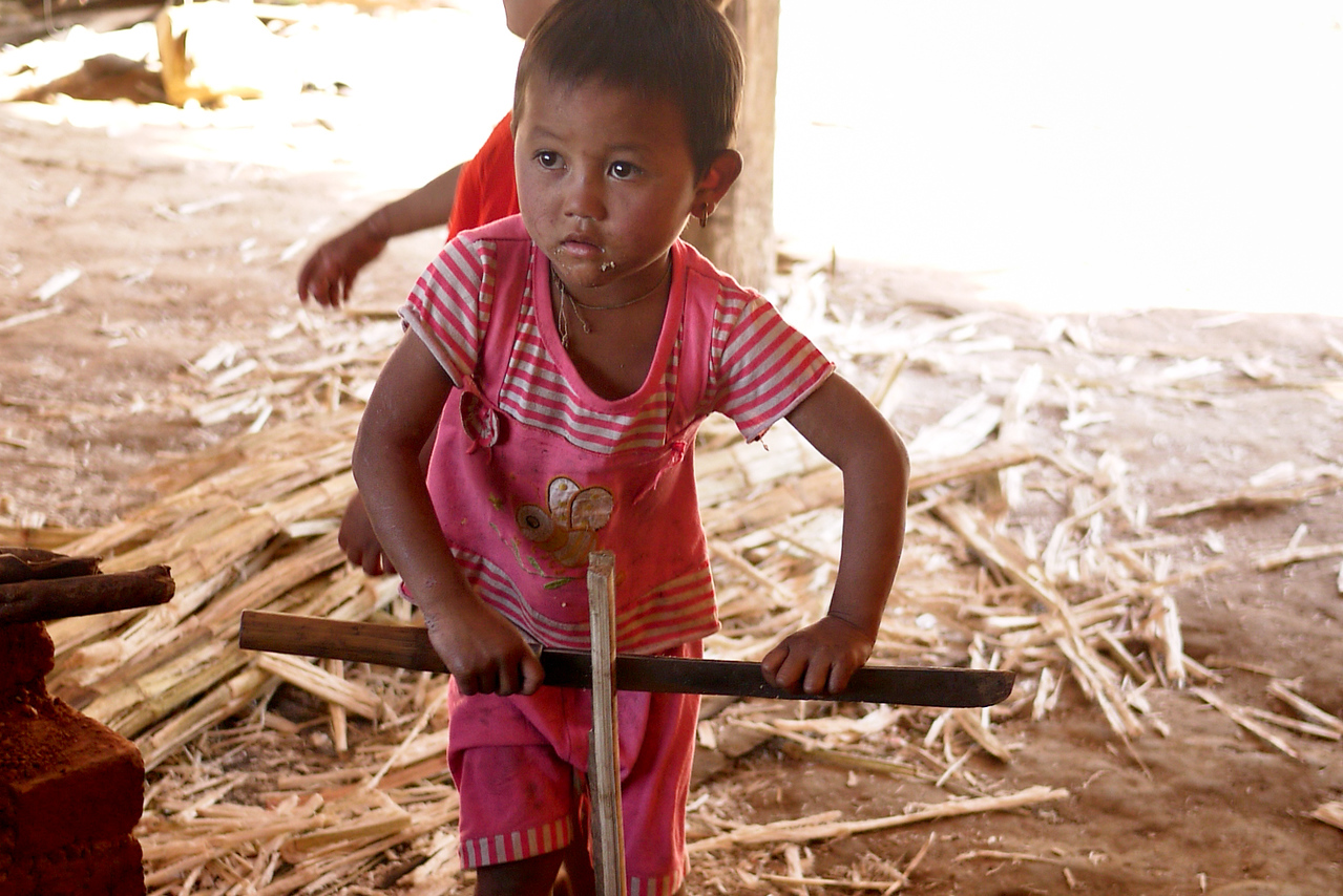 A little girl nonchalantly plays with a machete near Nyaung Shwe, on Inle Lake, Burma (Myanmar).