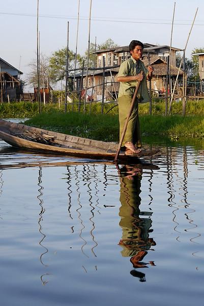 A man paddles home on Inle Lake, Burma (Myanmar).