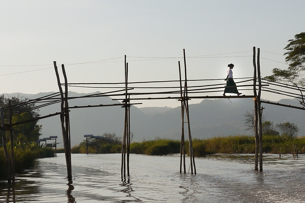 A women walks across a tall bridge in Inle Lake, Burma (Myanmar).