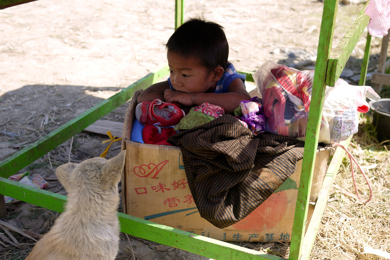 A child rests in a box under his mom's table at the market on Inle Lake, Burma (Myanmar).