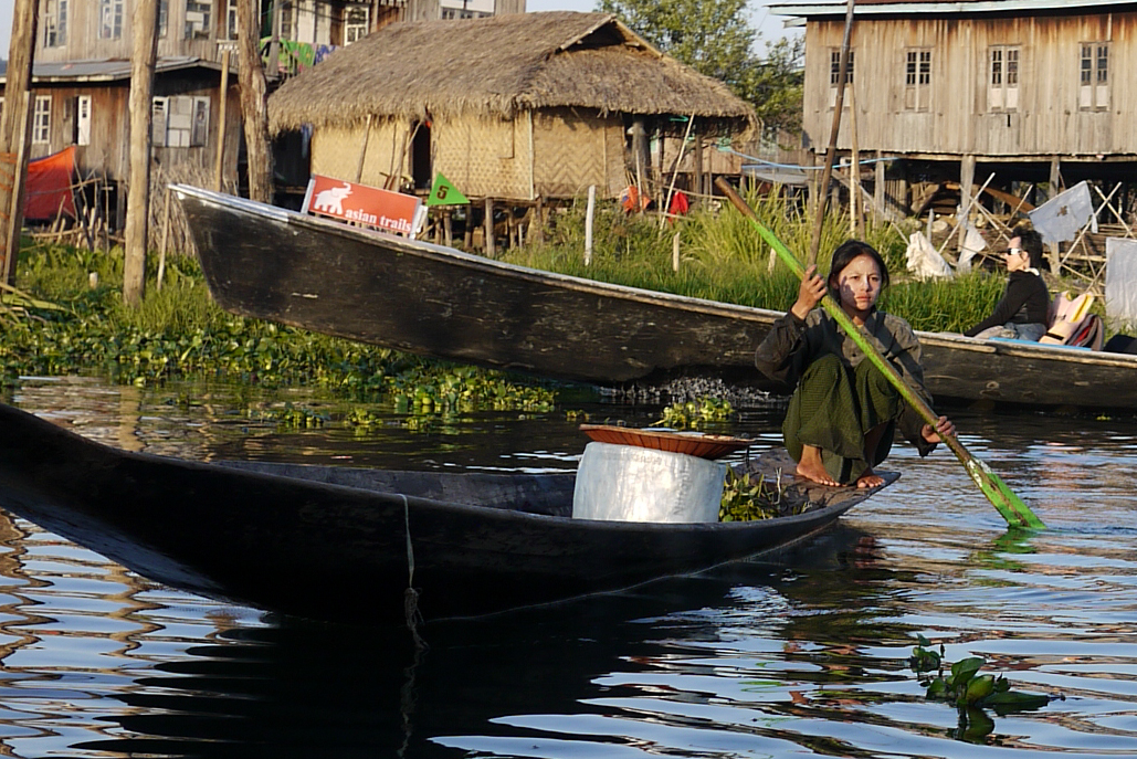 A young woman with thanaka rowing on Inle Lake, Burma (Myanmar).