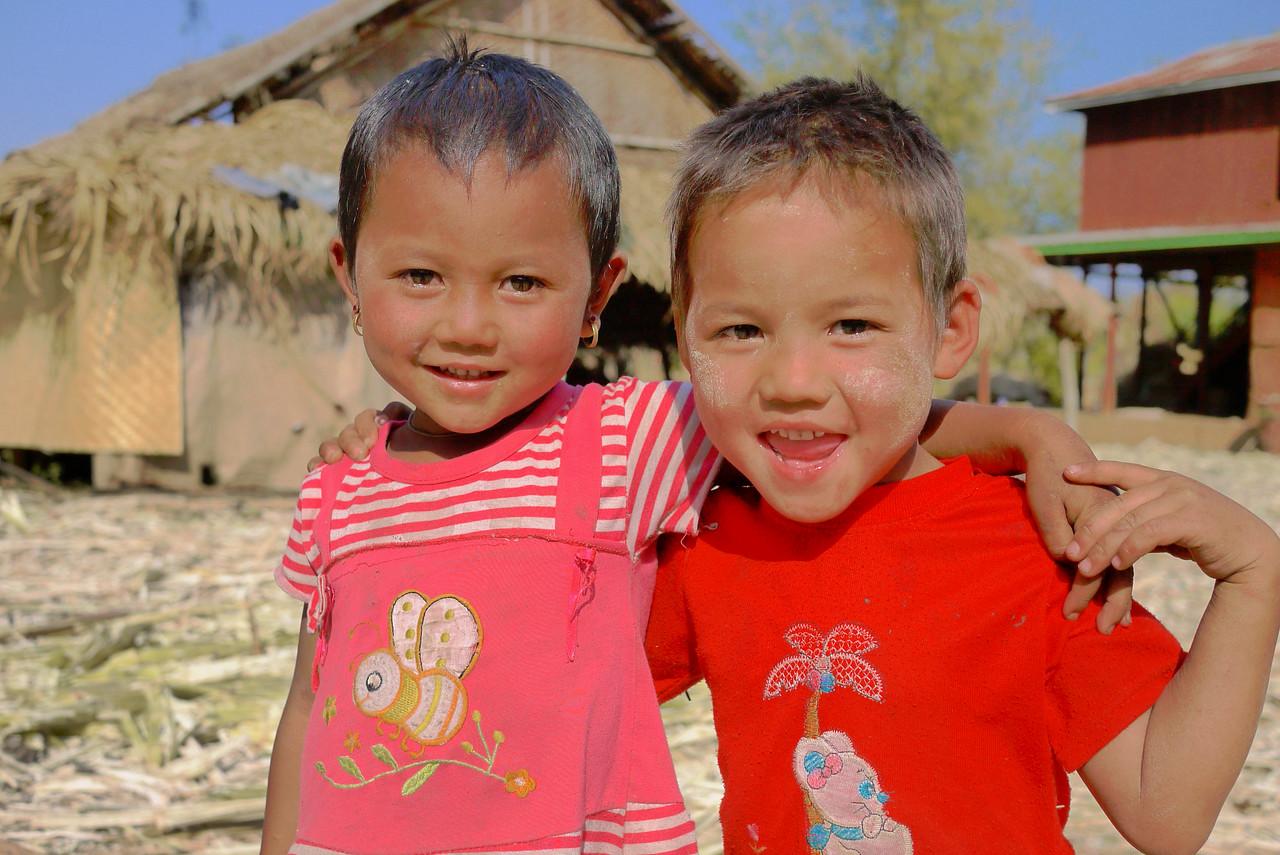 Two adorable kids play at their sugarcane factory Inle Lake, Burma (Myanmar).