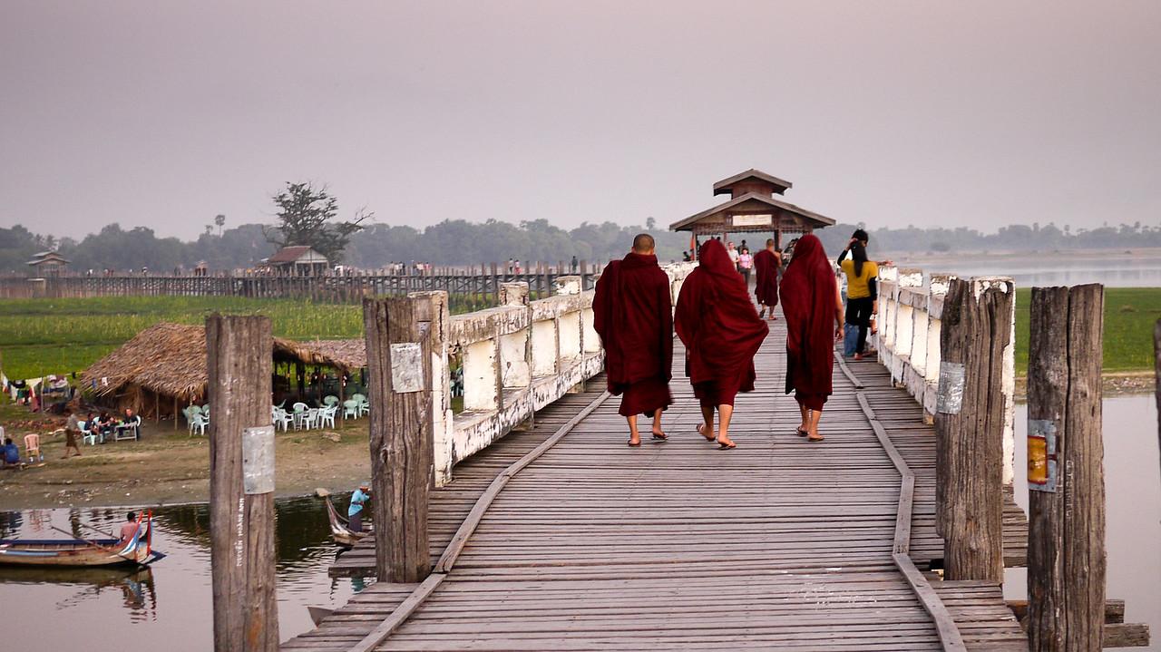 Monks cross U Bein Bridge at sunset.