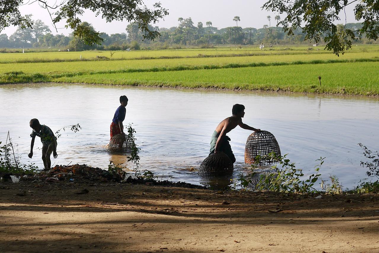 Men work in a small lake near the teak monastery on Innwa.