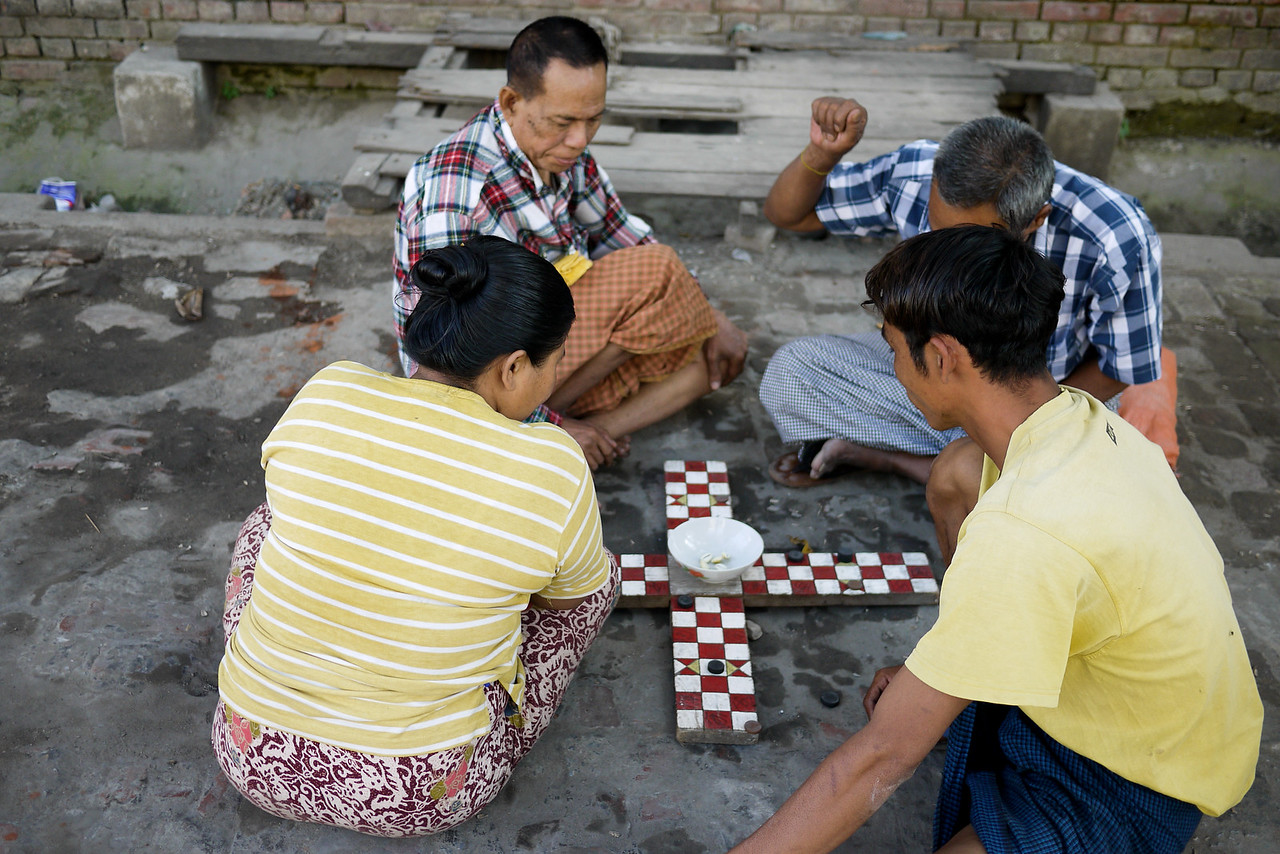 Men play a game on the streets of Mandalay, paying no heed to the passerbys as the game heated up.