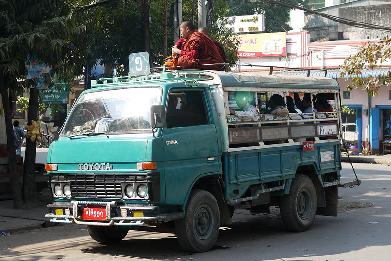 Two monks ride on the top of a truck in Mandalay, Burma.