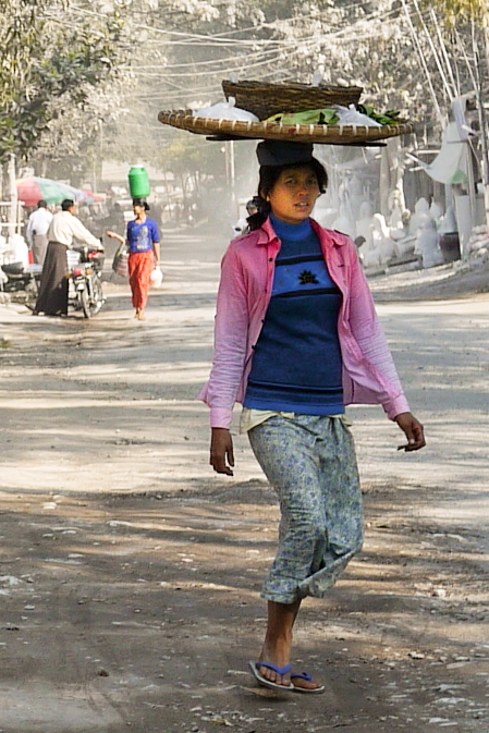 A woman balances snacks on her head for sale as she makes her way through the streets of Mandalay.
