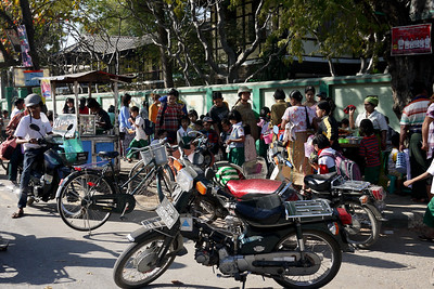 Traffic and kids as a school lets out in Mandalay.