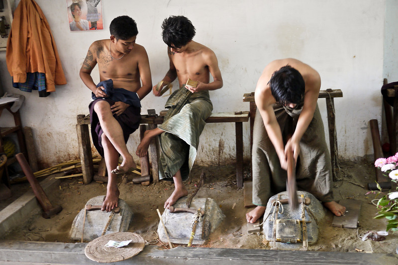 Men hammer the gold leaf and pound it flat at a shop in Mandalay.