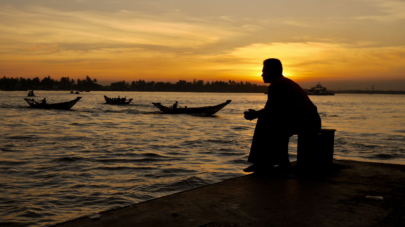 A man in Yangon takes in a quiet sunset over the river