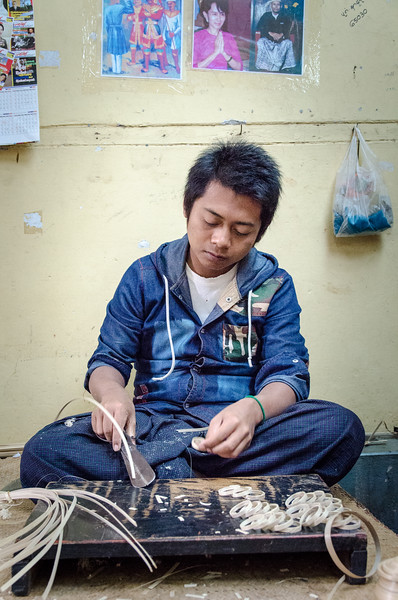 Bamboo is the base material for lacquerware. Here a man carves bamboo into strips.