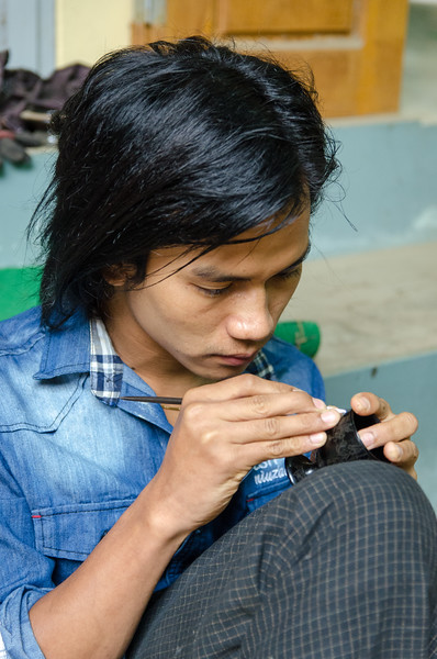 A young man does some intricate etching on a small lacquerware bowl.