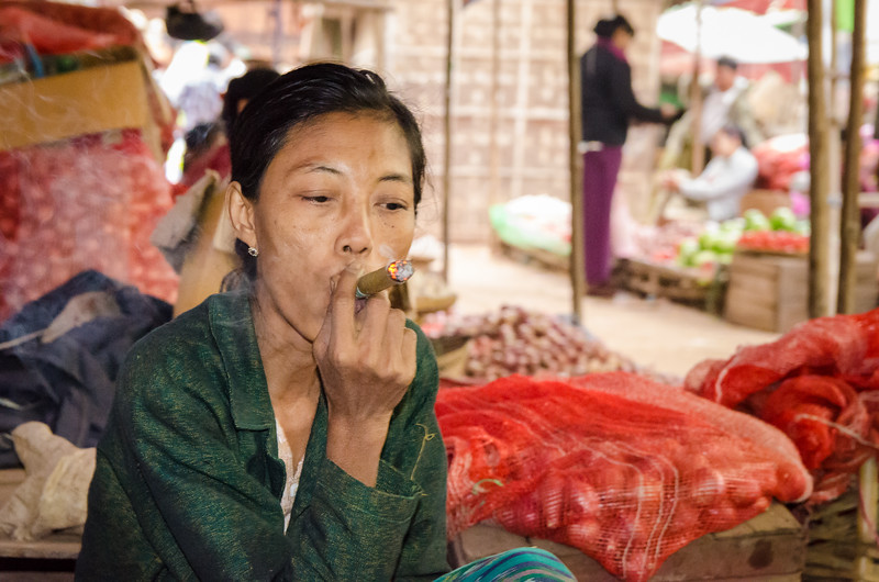Lady smoking a cigar in the market.  Nyaung U, Myanmar.