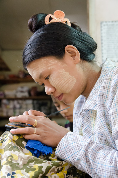 A lady etches lacquerware.